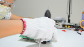 Technician is using screwdriver to loosen bolt screw to remove heat sink from electronic print circuit board. S stock footage