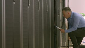 Technician using tablet pc while analysing server stock footage