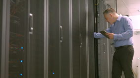Technician using tablet pc while analysing server. In high quality format stock video footage