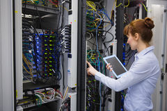 Technician using tablet pc while analysing server Royalty Free Stock Images