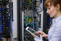 Technician using tablet pc while analysing server Stock Photo