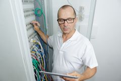 Technician using tablet in server room at data centre. Technician using tablet in server room at the data centre Royalty Free Stock Photography