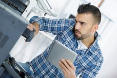 Technician using tablet to fix printer Royalty Free Stock Image