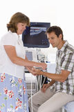 Technician using ultrasound treatment on patient?s wrist Royalty Free Stock Photos
