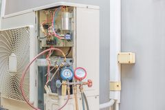 Technician vacuum pump evacuates and checking air conditioner , royalty free stock photo
