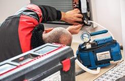 Technician vacuum pump evacuates and checking new air conditioner stock photos