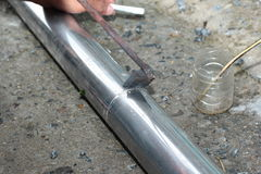 Technician is welding aluminium pipe by using soldering copper. Royalty Free Stock Image