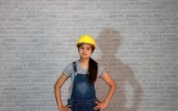 Technician woman ware white helmet with grey T-shirt and denim jeans apron dress standing akimbo. royalty free stock photo
