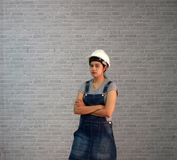 Technician woman ware white helmet with grey T-shirt and denim jeans apron dress standing forty five degree angle and hugging ches. T on grey brick pattern royalty free stock images