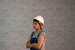 Technician woman ware white helmet with grey T-shirt and denim jeans apron dress standing forty five degree angle and hugging ches. T on grey brick pattern royalty free stock photography