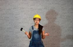 Technician woman ware yellow helmet with grey T-shirt and denim jeans apron dress standing and rubber hammer in right hand, palms royalty free stock photo