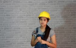 Technician woman ware yellow helmet with grey T-shirt and denim jeans apron dress standing and steel hammer in two hands. stock photography