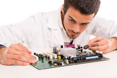 Technician at work. A computer engineer or technician, working on a computer motherboard Royalty Free Stock Images