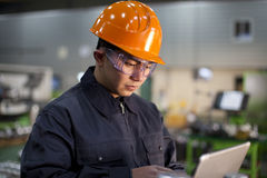 Technician at work in factory. Technician working in factory using laptop Royalty Free Stock Photo