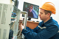 Technician worker adjusting video surveillance system. Technician worker agjusting position and signal of video surveillance camera system Royalty Free Stock Photos