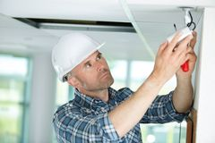 Technician worker adjusting video surveillance system. Fitting Stock Photo