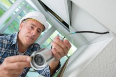 Technician worker installing video surveillance camera on wall. Fitting Royalty Free Stock Images