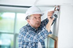 Technician worker installing video surveillance camera on wall. Cctv Stock Image
