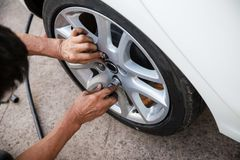 Technician worker is screwing the wheel bolt with a manual wrench. maintenance and Inspection car concept. check up and fixing veh stock photo