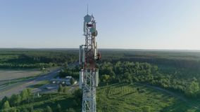 Technician worker servicing cellular antenna, drone view of telecommunication system tower stock video footage