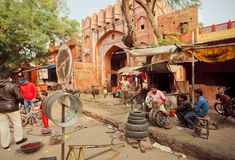 Technician workers repairing wheels for cars and bicycles in a street shop of indian city Royalty Free Stock Photography