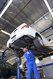 Technician working on car at automobile repair shop Royalty Free Stock Image