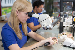 Technician working on dental prosthesis under a microscope Royalty Free Stock Photo