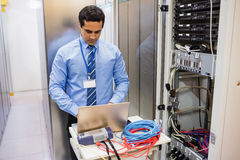 Technician working on laptop. Focused technician working on laptop in server room Royalty Free Stock Photography