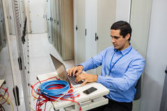 Technician working on laptop. Focused technician working on laptop in server room Royalty Free Stock Photo