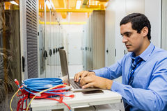 Technician working on laptop. Focused technician working on laptop in server room Royalty Free Stock Images