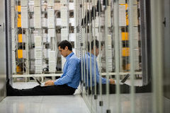 Technician working on laptop in hallway. Of server room Royalty Free Stock Image