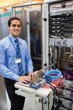 Technician working on laptop. Portrait of happy technician working on laptop in server room Stock Photo