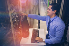 Technician working on personal computer while analyzing server. In server room Stock Photography
