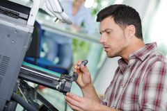 Technician working on printer. Man royalty free stock images