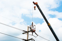 Technician works in a bucket high up on a power pole stock photo