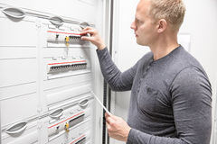 Technician works in large electric fuse cabinet Stock Image