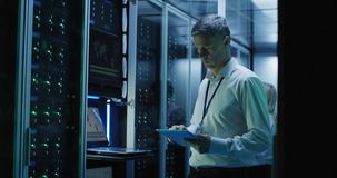 Technician works on a tablet in a data center. Medium shot of technician working on a tablet in a data center full of rack servers running diagnostics and stock photo