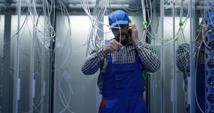 Technician works talking on phone in data center. Medium shot of technician working with cables in a data center full of rack servers running diagnostics and royalty free stock photo