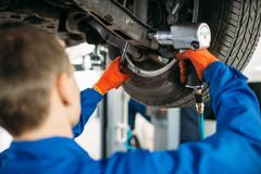 Technician with a wrench repair car suspension. Technician with a wrench repair the suspension, car on the lift. Automobile service, vehicle maintenance royalty free stock photos