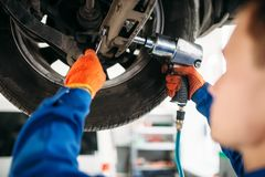 Technician with a wrench repair car suspension. Technician with a wrench repair the suspension, car on the lift. Automobile service, vehicle maintenance stock photo