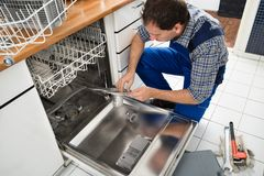 Technician writing on clipboard in kitchen. Male Technician Sitting Near Dishwasher Writing On Clipboard In Kitchen Stock Image