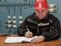 Technician writing data in the power plant control center Royalty Free Stock Images