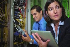 Technicians analyzing rack mounted server Stock Image