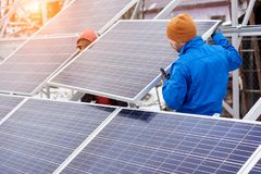 Technicians in blue suits mounting photovoltaic solar panels on roof of modern house. Solar modules as ecological renewable energy sources. Alternative Stock Image