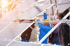 Technicians in blue suits mounting photovoltaic solar panels on roof of modern house. Team work. Technicians in blue suits mounting photovoltaic solar panels on Stock Image