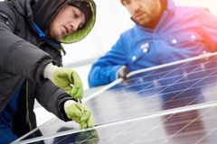 Technicians in blue suits mounting photovoltaic solar panels on roof of modern houses. Solar modules as ecological renewable energy sources. Alternative stock images