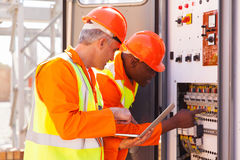 Technicians checking transformer. Two experienced industrial technicians checking transformer Stock Images