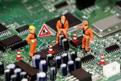 Technicians on circuit board stock photo