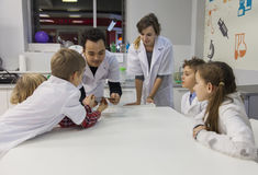 Technicians demonstrate to kids the experiment with metal filings and a magnet Royalty Free Stock Images