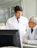 Technicians Discussing In Laboratory. Male technicians discussing in laboratory Stock Image